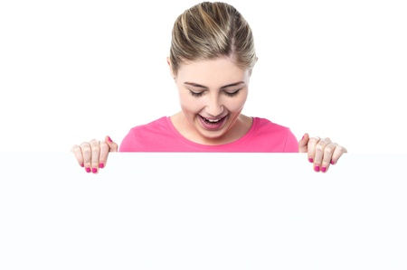 Smiling young girl posing from behind a blank whiteboard photo