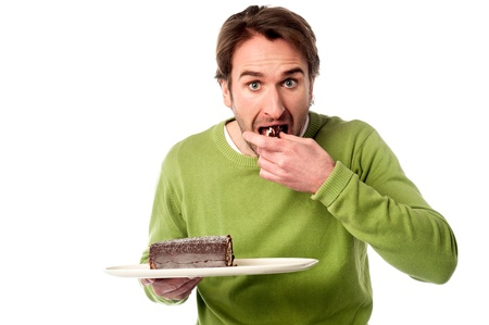 Young man eating chocolate cake in hurry photo