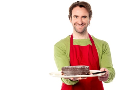 Young male chef presenting birthday cake photo