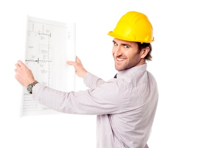 Handsome male engineer holding out construction plan photo