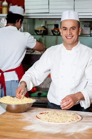 pizza base: Chef sprinkling grated cheese over pizza base Stock Photo