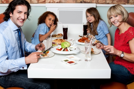 Family enjoying their dinner at a restaurant photo