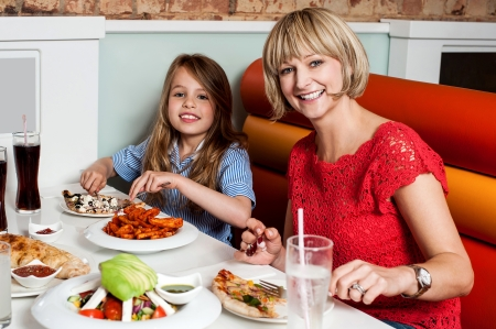 Sweet daughter with her mother in a restaurant photo
