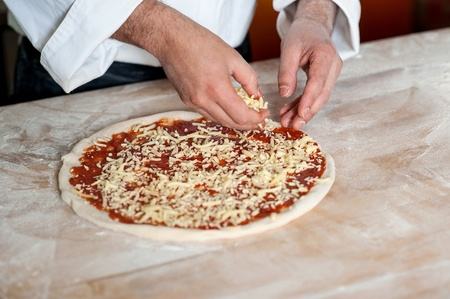 pizza base: Chef spreading cheese toppings on pizza base