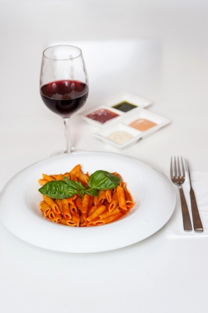 Yummy pasta served with sauces and red wine