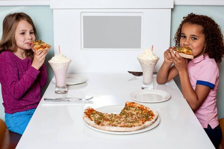 Cute girls eating pizza together in a restaurant photo