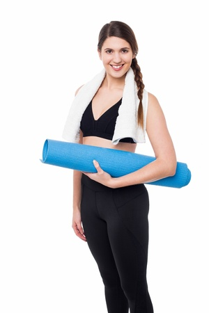 Attractive gym trainer posing with a mat photo