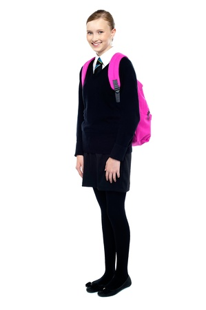 Cheerful girl in school uniform carrying backpack