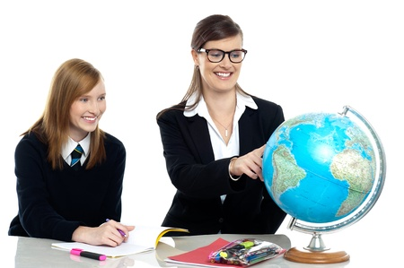 Teacher pointing out a country on the globe Stock Photo - 21326272