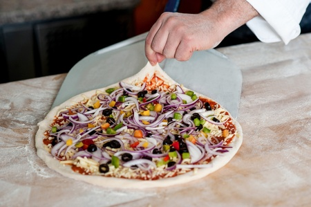 Cropped image of male chef handling pizza photo