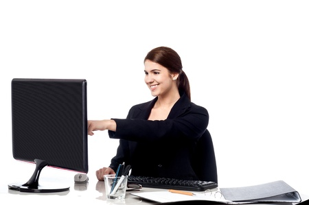 Smart female executive pointing at computer screen photo