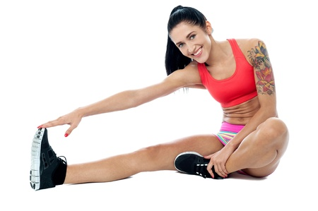 touching toes: Fit athletic woman doing stretching exercise
