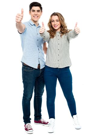 Love couple gesturing thumbs up to camera Stock Photo - 21332520