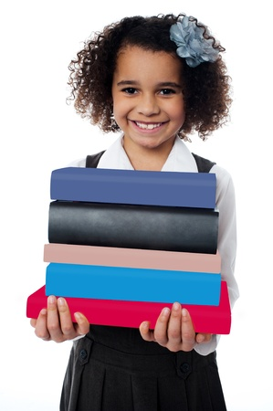 Isolated little girl carrying pile of books photo