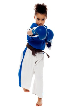 bout: Little karate girl throwing right arm punch Stock Photo