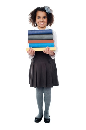 Smiling pretty kid holding pile of books photo