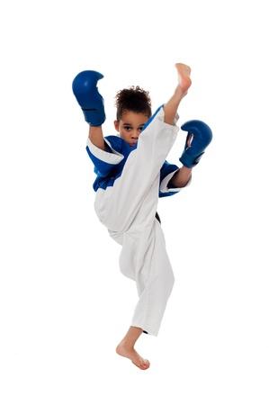 Active little girl practicing upper kick photo