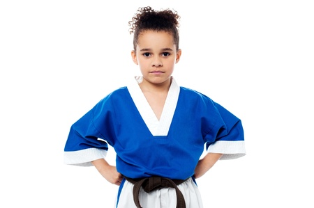 Confident young karate kid with hands on waist photo