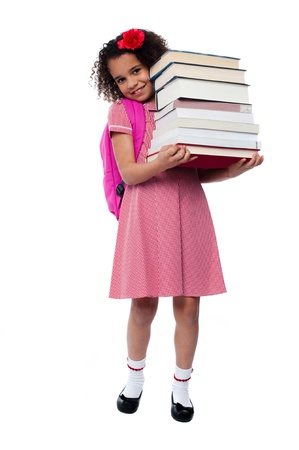 Smiling little girl holding pile of school books photo
