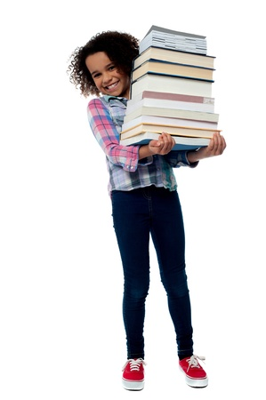 Smiling little girl holding stack of school books photo