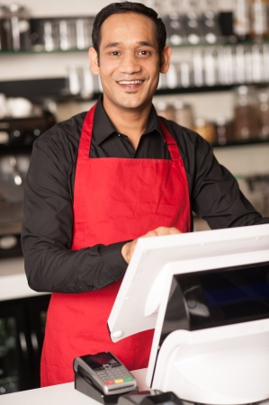 billing: Asian barista staff at the cash counter confirming order.