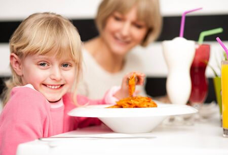 Cute girl kid enjoying meal and juice in restaurant with her mother. photo