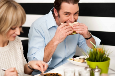 Man eating sandwich in a restaurant along with his wife. photo