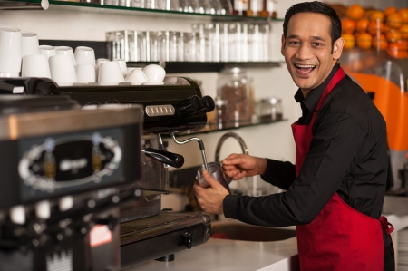 barista: Cheerful male staff preparing customers order.