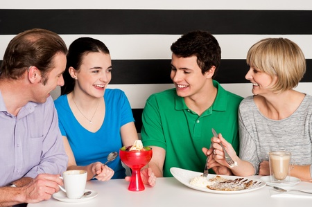 relishing: Cheerful family of four relishing delicious eatables and dessert. Stock Photo