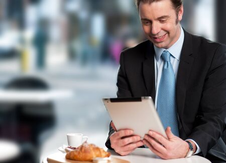 Corporate male manager reviewing business updates on his tablet device photo