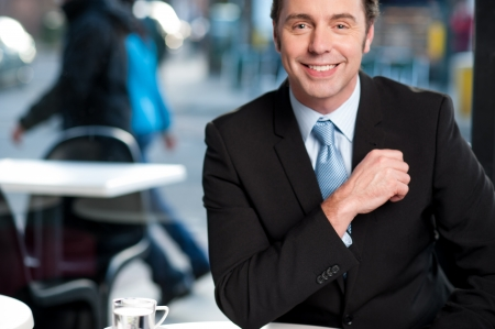 happy businessman: Handsome businessman in open-air cafe.
