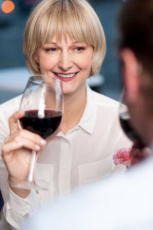 cherishing: Couple cherishing memories while drinking red wine in restaurant.