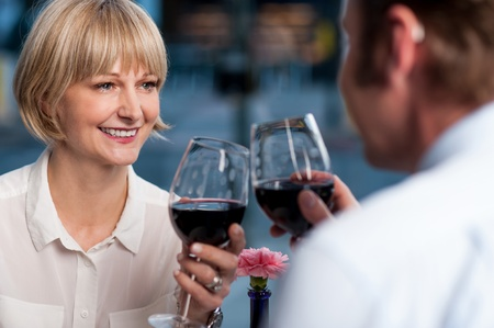 woman drinking wine: Mid adult couple toasting in restaurant  Cheers to our love