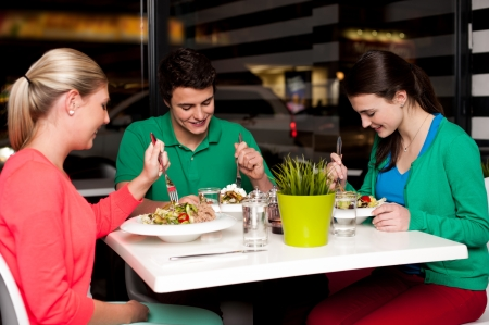 Family of three enjoying meal at restaurant. photo