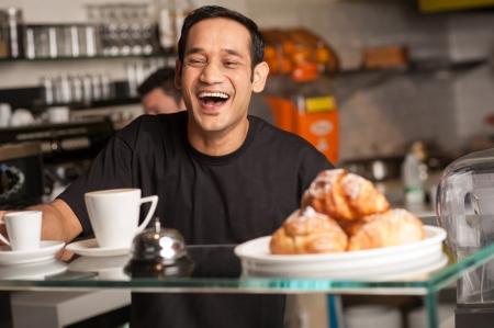 El personal en el restaurante estalla de risa para una broma agrietada por el cliente. Foto de archivo