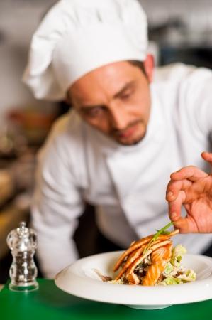 chef cocinando: Cocinero que agrega toque final a delicioso salm�n al horno delicioso. Foto de archivo