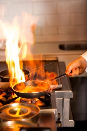 chef cocinando: Cocinero que cocina con la llama en una sart�n en una estufa de la cocina. Foto de archivo
