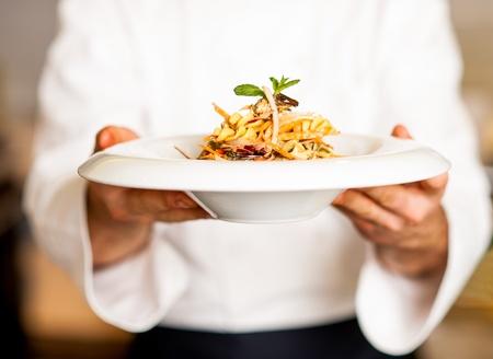 シェフは、口の水まきのパスタサラダ、提供する準備ができて保持します。