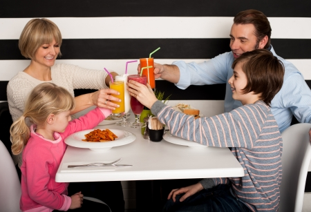 people eating at restaurant: Its celebration time. Family toasting smoothies. Stock Photo