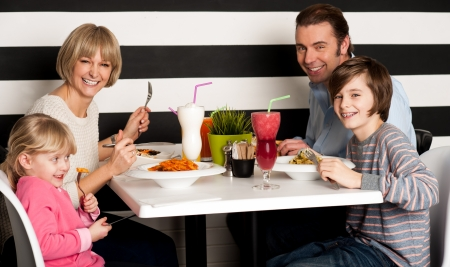 Father and mother with children enjoying meal in restaurant. photo