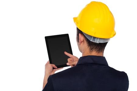 ingeniero civil: Joven dispositivo de pantalla t�ctil de explotaci�n trabajador de la construcci�n Foto de archivo