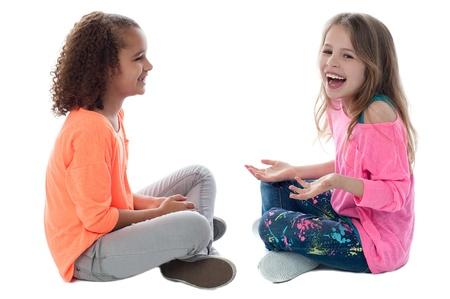 Mooie meisjes zitten op de vloer en spelen