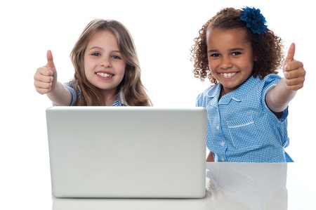 School kids with laptop gesturing thumbs up Stock Photo - 21332657