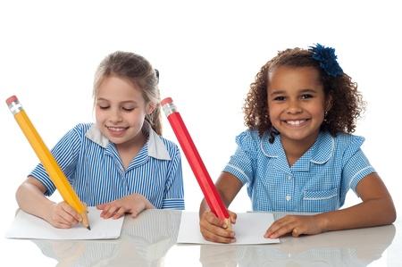 ni�os escribiendo: Sonriente ni�os escriben su examen anual Foto de archivo
