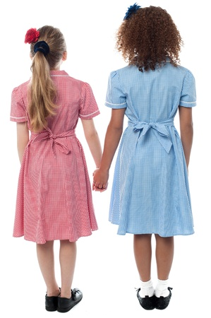 cute little girls: School girls holding hands, rear view shot