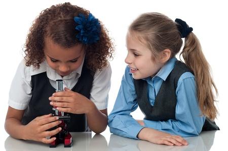 School girls using a microscope in lab photo