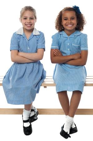 zapatos escolares: Ni�as de la escuela alegre que presenta con confianza Foto de archivo