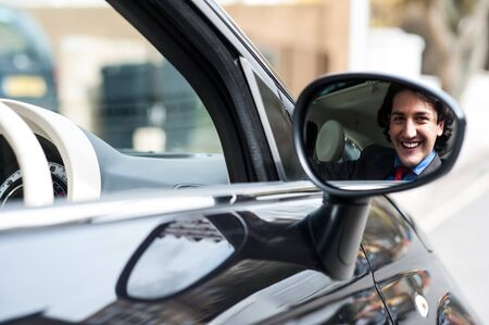rear view mirror: Empresario sonriendo en el espejo retrovisor Foto de archivo