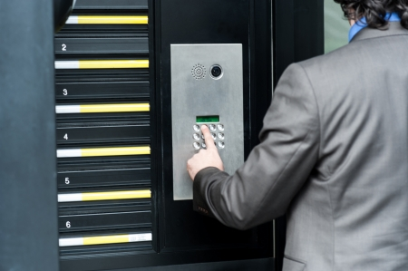 access control: Businessman entering safe code to unlock the door Stock Photo