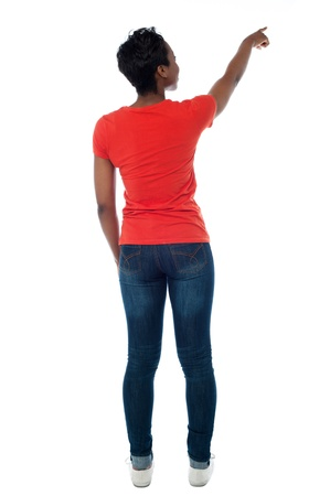 Back pose of a woman pointing at something photo